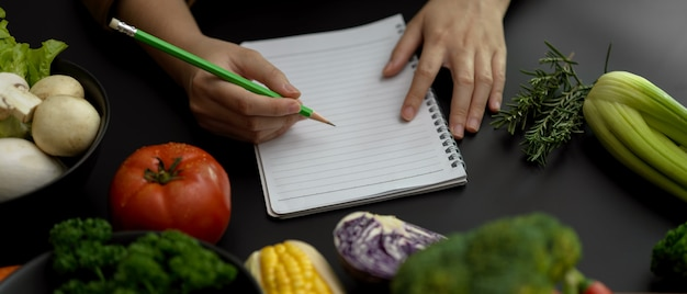 Studentin, die rezeptnotizen auf leerem notizbuch auf schwarzem küchentisch im kochkurs nimmt