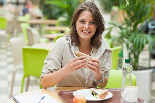 Studentin, die sandwich in der cafeteria isst