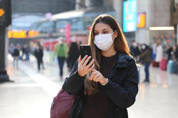 Studentin, die schutzmaske trägt, die ticket online mit smartphone kauft