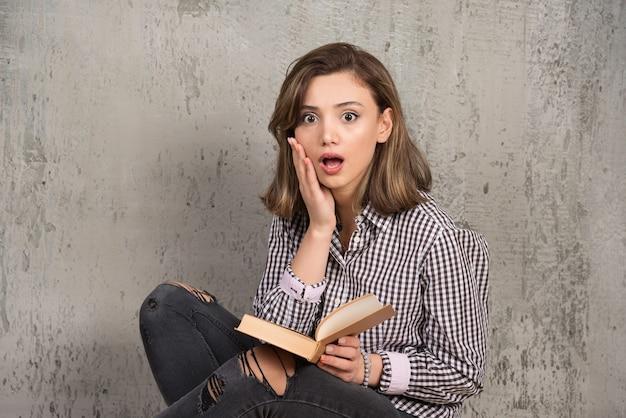 Studentin, die über geschichte schockiert wird.