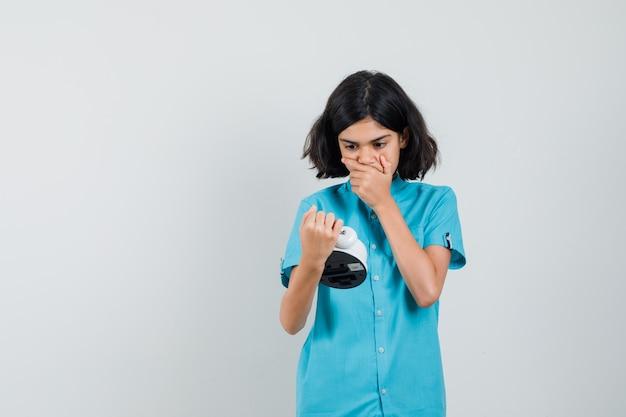 Studentin, die uhr im blauen hemd betrachtet und stressig schaut
