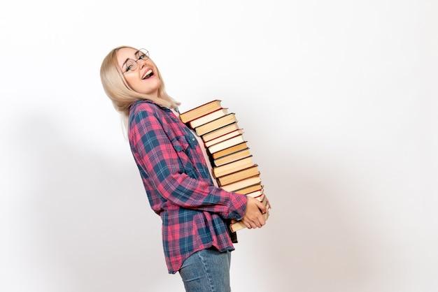 Studentin, die verschiedene schwere bücher auf weiß hält