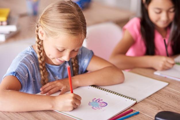 Studentin, die während des unterrichts zeichnet