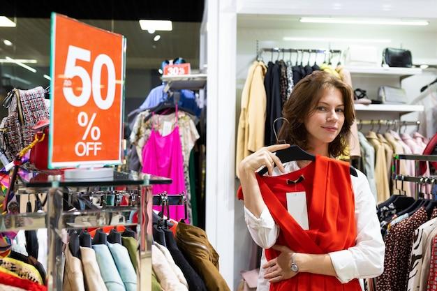 Studentin geht im second-hand-laden mit großem verkauf günstig einkaufen