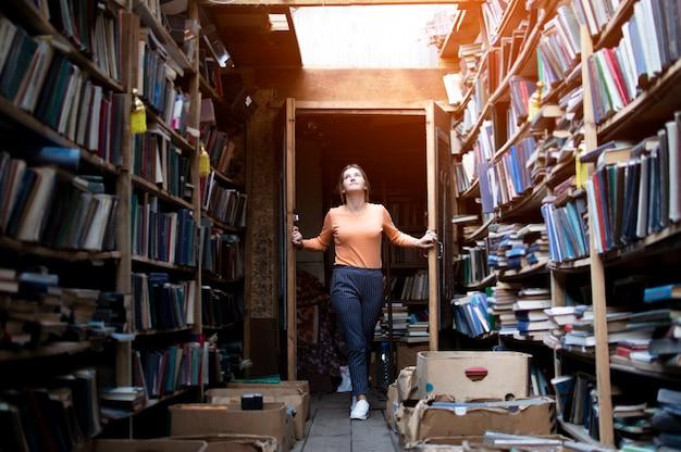 Studentin geht in die bibliothek für bücher, sie öffnet die tür, bildungskonzept