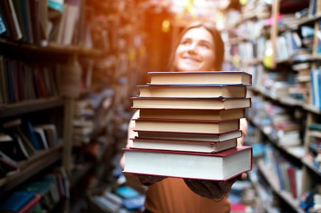 Studentin hält einen stapel bücher in der bibliothek, sie sucht nach literatur und bietet an zu lesen, eine frau bereitet sich auf das studium vor, wissen ist macht, buchhändler im buchladen