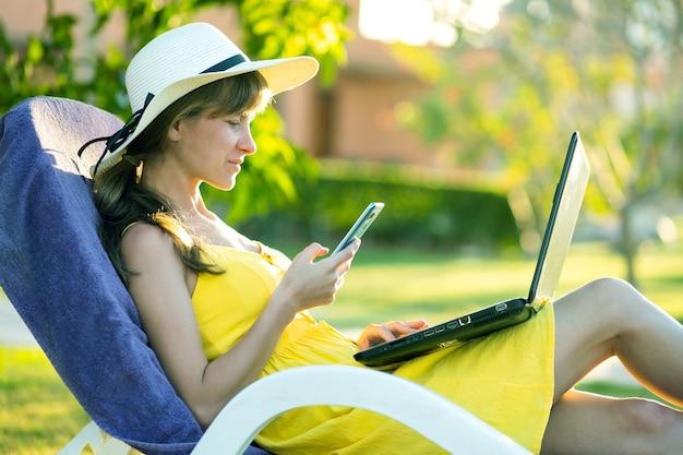 Studentin im gelben sommerkleid, das auf grünem rasen im sommerpark ruht, der auf computer-laptop-sms auf dem handy studiert.