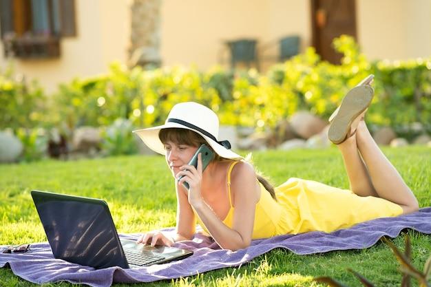 Studentin im gelben sommerkleid, die auf grünem rasen im sommerpark ruht und auf computer-laptop studiert, der sich auf dem handy unterhalten hat. geschäfte machen und während des quarantänekonzepts lernen.