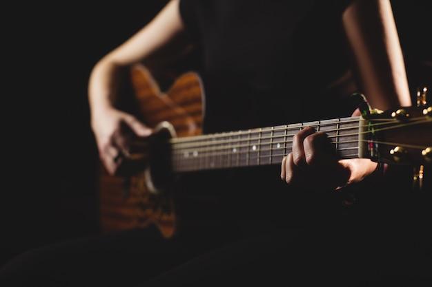 Studentin im mittelteil, die gitarre spielt