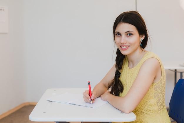 Studentin im teenageralter, die im klassenzimmer studiert und auf kamera schaut und lächelt