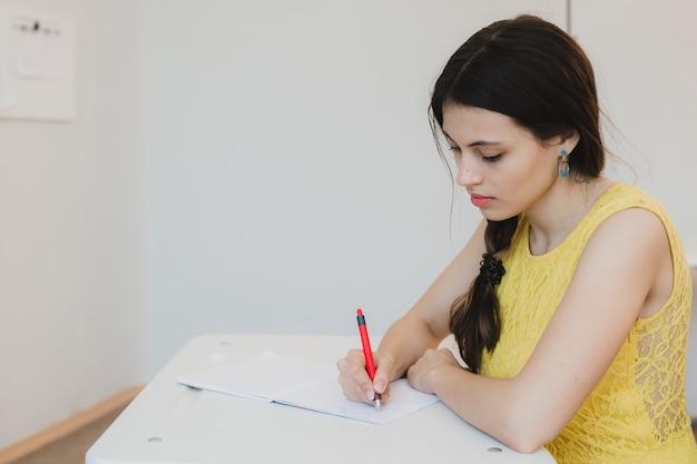 Studentin im teenageralter, die im klassenzimmer studiert