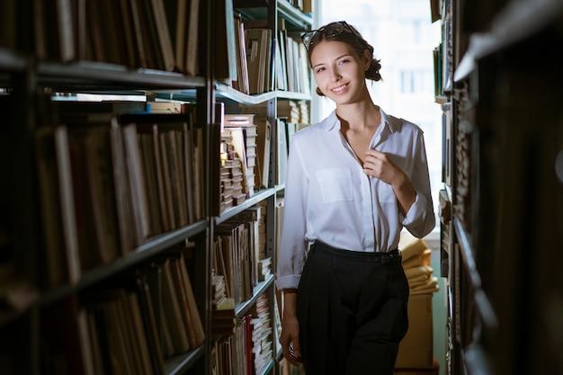 Studentin im weißen hemd steht zwischen den reihen in der bibliothek, bücherregale im wert von büchern. dunkles foto