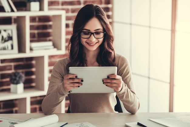Studentin in den brillen benutzt eine digitale tablette.