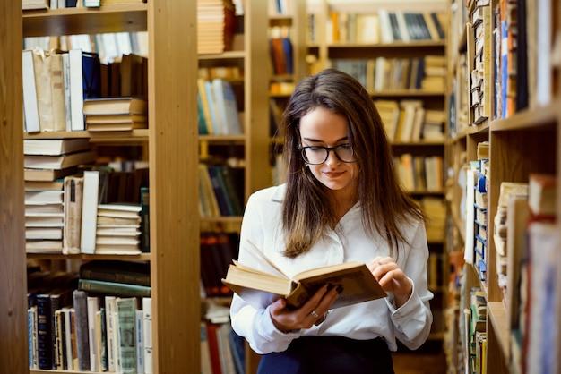 Studentin in der bibliothek, die ein buch liest