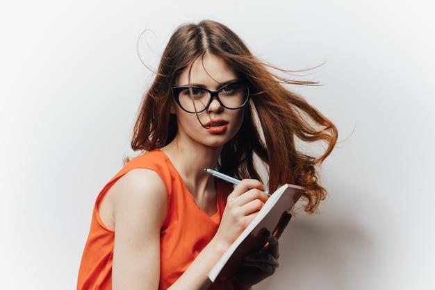 Studentin in einem sommerkleid mit einem notizbuch und einer brille auf ihrem gesicht weiß
