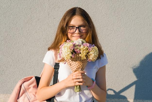 Studentin in gläsern mit rucksack und blumenstrauß