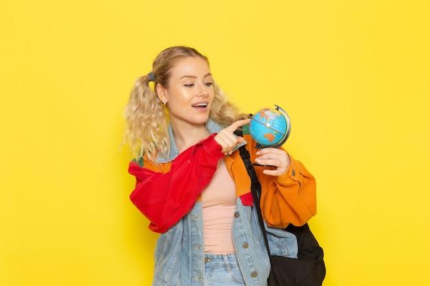 Studentin jung in modernen kleidern, die kleine runde kugel auf gelb halten
