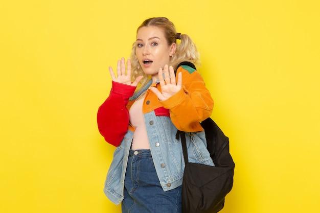 Studentin jung in modernen kleidern, die mit vorsicht auf gelb posieren