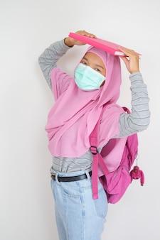 Studentin junges mädchen trägt rosa hijab und maske hält bücher auf weißem hintergrund