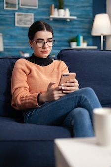 Studentin liegt bequem auf dem sofa im wohnzimmer, während sie mit einem modernen smartphone eine nachricht an ihren freund schreibt. teenager im chat im sozialen netzwerk mit blick auf den telefonbildschirm lächeln