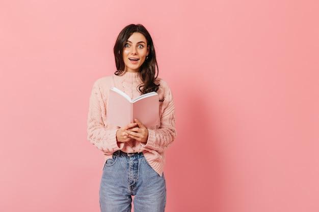 Studentin liest buch in rosa umschlag. dame, die enthusiastisch kamera auf lokalisiertem hintergrund betrachtet.