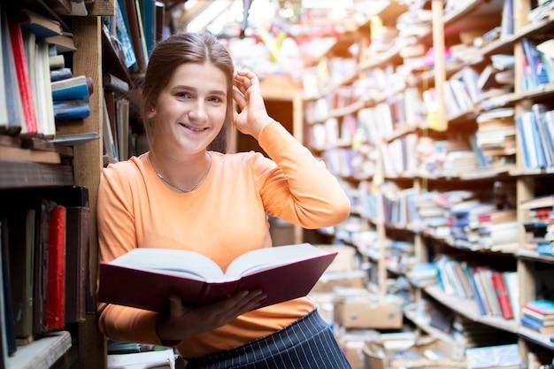 Studentin liest ein buch in der alten bibliothek, eine frau sucht nach informationen in den archiven