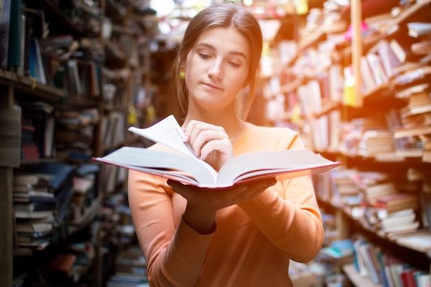 Studentin liest ein buch in der bibliothek, blättert um und bürstet informationen