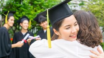 Studentin mit den Abschlusskleidern und -hut umarmen das Elternteil in der Glückwunschzeremonie.