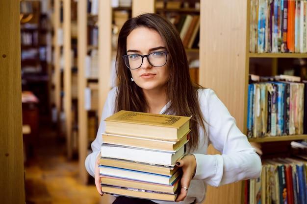 Studentin mit einem großen stapel bücher in der bibliothek