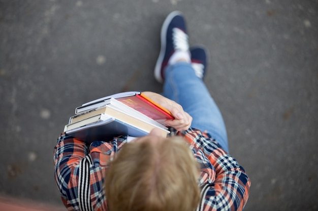 Studentin mit einem haufen lehrbücher und notizbücher