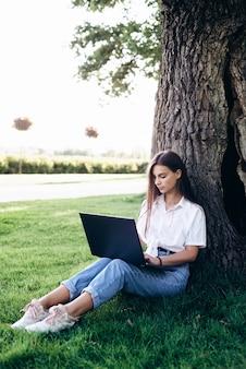 Studentin mit einem laptop im freien sitzt auf dem rasen im park
