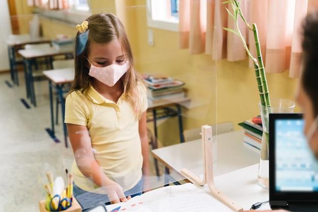 Studentin mit einer maske, die dem lehrer durch einen methacrylatschirm hausaufgaben übergibt