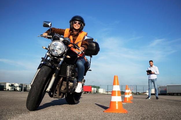Studentin mit helm, der motorradstunden nimmt und fahrt übt.