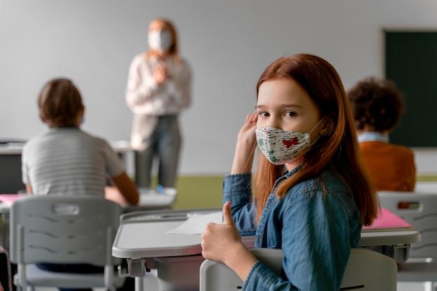 Studentin mit medizinischer maske, die schule besucht