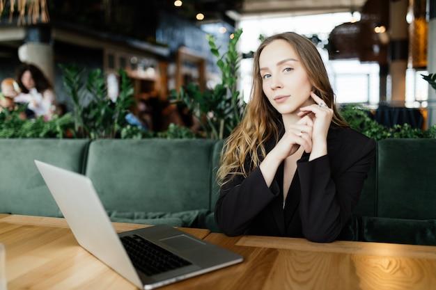 Studentin mit niedlichem lächeln, das etwas auf netbook tastet, während sie sich nach vorlesungen in der universität entspannt, schöne glückliche frau, die während der kaffeepause in der café-bar am laptop arbeitet