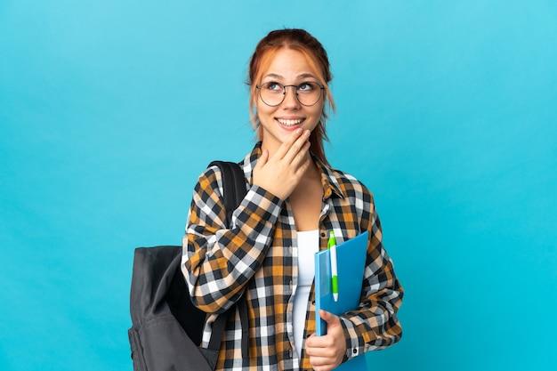 Studentin russische frau isoliert auf blau, das beim lächeln nach oben schaut