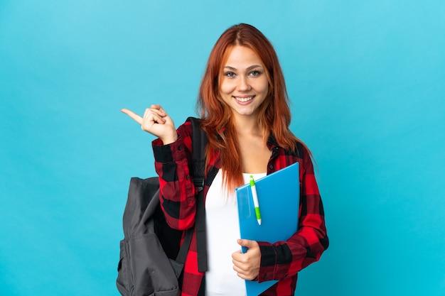 Studentin russische frau isoliert auf blau halten copyspace imaginär auf der handfläche, um eine anzeige einzufügen