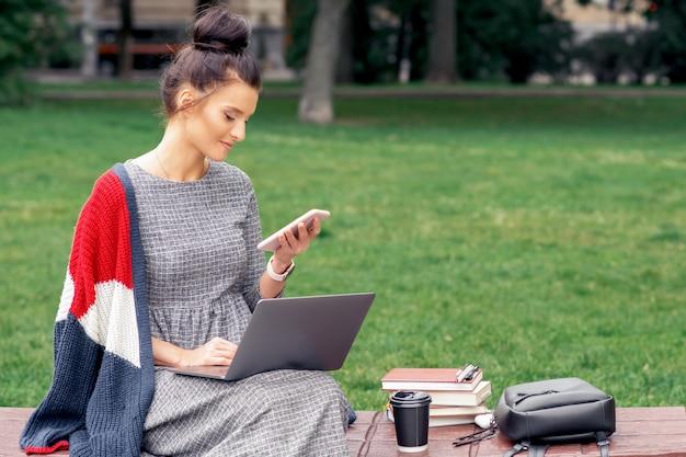 Studentin schaut auf smartphone mit laptop auf einer holzbank im park.