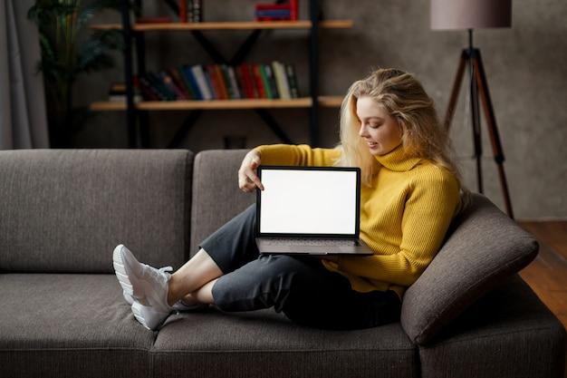 Studentin sitzt auf dem sofa und hält den laptop, der den scheinbildschirm betrachtet, online-lernen auf pc, e lernen. nahaufnahme