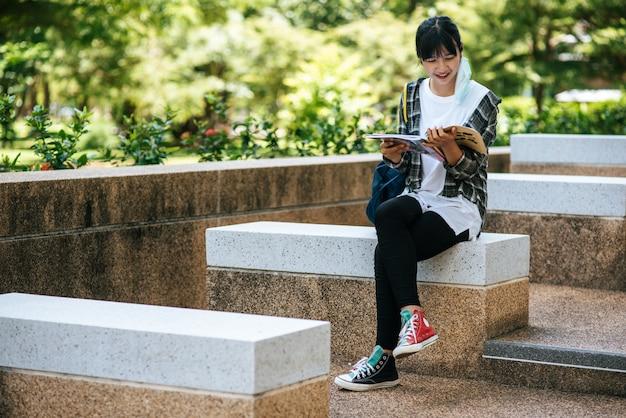 Studentin sitzt auf der treppe und liest ein buch.