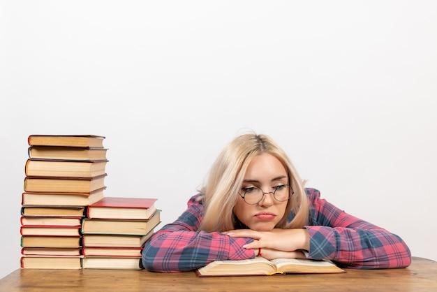Studentin sitzt mit büchern, die sich auf weiß müde fühlen