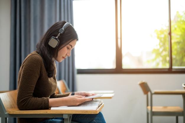 Studentin sitzt und hört musik im klassenzimmer