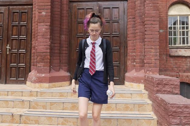 Studentin teenager in uniform mit rucksack, schulhintergrund bauen. zurück zur schule, zurück zum college, bildung, teenager-konzept