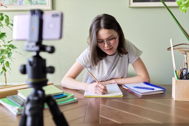 Studentin teenager online studieren mit smartphone, videokonferenzen, videoanruf, fernunterricht, lernen zu hause