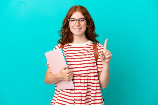 Studentin teenager rothaarige mädchen auf blauem hintergrund isoliert auf eine tolle idee zeigen