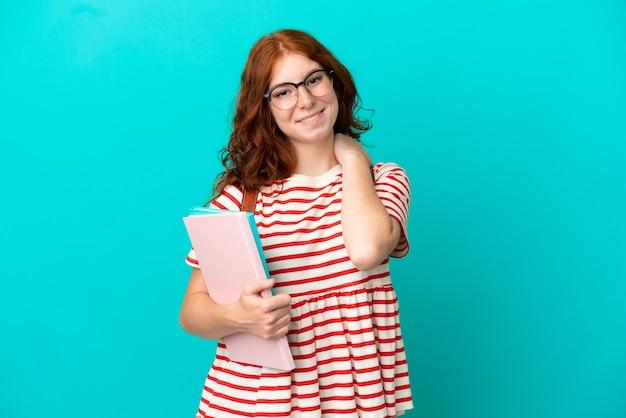 Studentin teenager rothaarige mädchen auf blauem hintergrund lachend isoliert