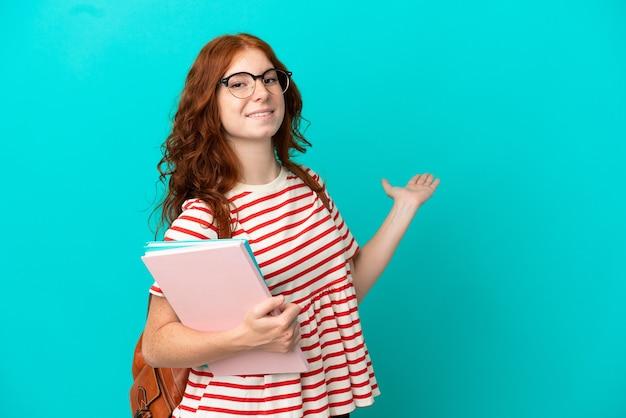 Studentin teenager rothaarige mädchen isoliert auf blauem hintergrund hände zur seite ausstrecken für die einladung zu kommen