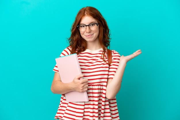 Studentin teenager rothaarige mädchen isoliert auf blauem hintergrund mit zweifeln beim heben der hände