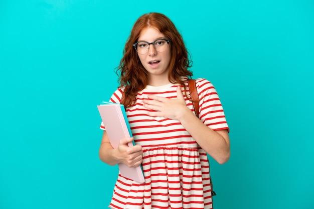 Studentin teenager rothaarige mädchen isoliert auf blauem hintergrund überrascht und schockiert, während sie nach rechts schaut