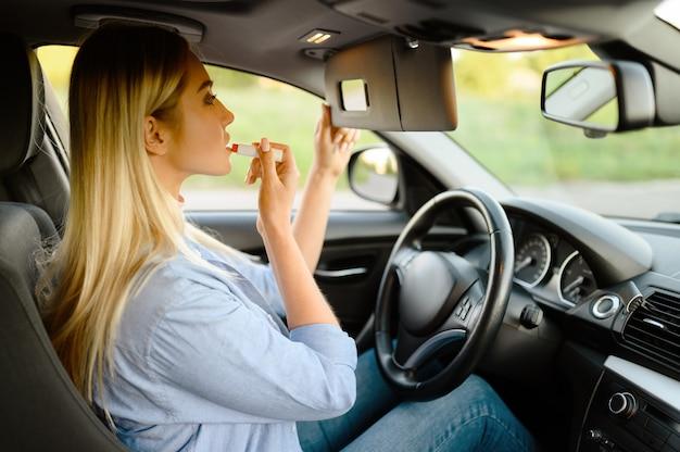 Studentin trägt make-up im auto auf, unterricht in der fahrschule. mann, der dame lehrt, fahrzeug zu fahren.